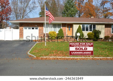 American flag pole Real estate sold (another success let us help you buy sell your next home) sign suburban brick ranch style home white picket fence blacktop driveway autumn blue sky day USA - stock photo