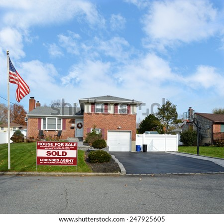 American flag pole Real estate sold (another success let us help you buy sell your next home) sign Suburban Brick Snout style home landscaped yard residential neighborhood USA blue sky clouds - stock photo