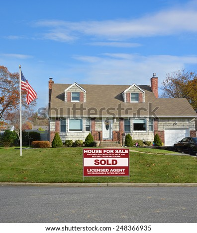 American flag pole Real estate sold (another success let us help you buy sell your next home) sign Suburban Cape Cod home landscaped beautiful autumn day residential neighborhood USA - stock photo