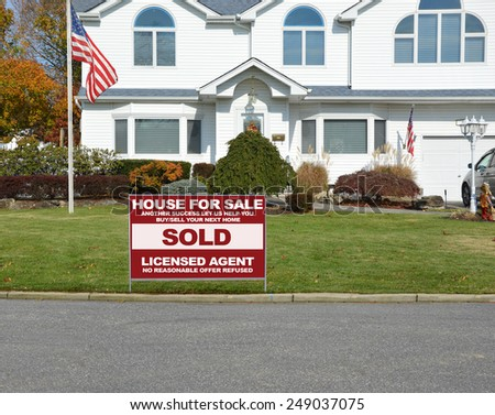 American flag pole Real estate sold (another success let us help you buy sell your next home) sign closeup of suburban mcmansion autumn day residential neighborhood USA
