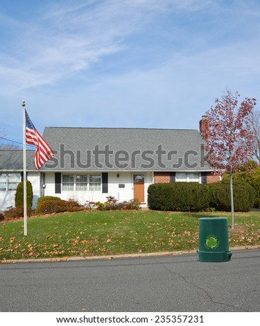American flag pole Recycle trash container on street in front of suburban bungalow style home autumn season residential neighborhood blue sky clouds USA - stock photo
