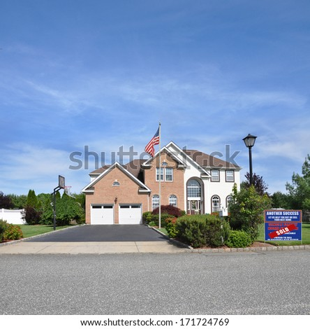 American flag pole Sold Real Estate Sign 'another success let us help you buy sell you next home' Suburban McMansion style brick home Landscaped sunny residential neighborhood USA blue sky clouds - stock photo