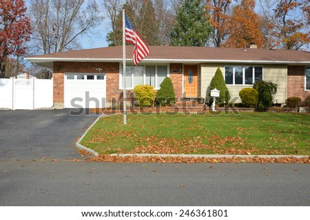 American flag pole suburban brick ranch style home white picket fence blacktop driveway autumn blue sky day residential neighborhood USA - stock photo