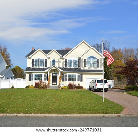 American flag pole Suburban McMansion home autumn day blue sky residential neighborhood USA - stock photo