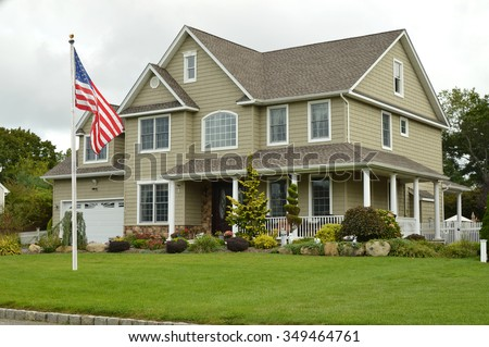American flag pole Suburban McMansion style home overcast cloudy day residential neighborhood USA - stock photo