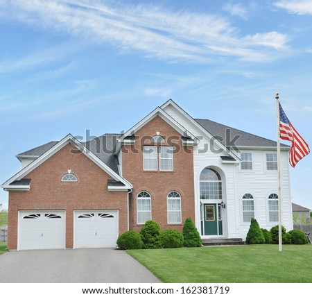 American Flag Pole Suburban McMansion Two Car Garage Brick Home Blue Sky Clouds Residential Neighborhood USA - stock photo