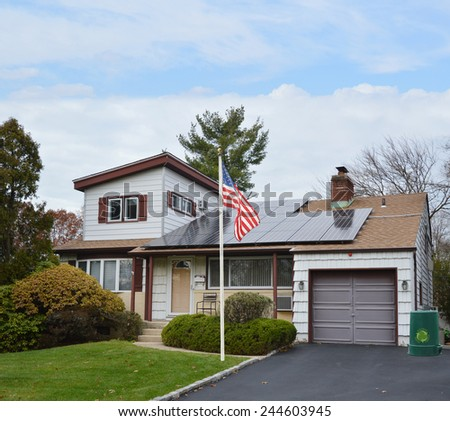 American flag pole Suburban Ranch style home with solar panel on roof residential neighborhood USA blue sky clouds - stock photo