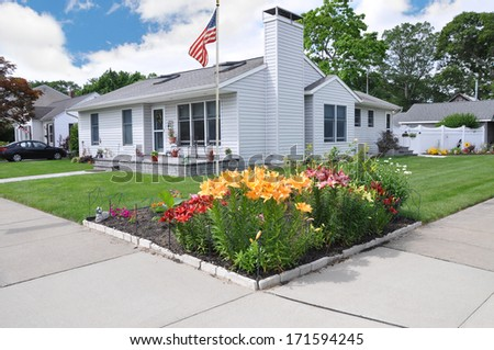 American Flag Pole Tulips Suburban Home Landscaped Residential Neighborhood USA Blue Sky Clouds - stock photo