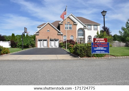 American Flag pole Welcome open house real estate sign curbside front yard Suburban McMansion style brick home Landscaped sunny residential neighborhood USA blue sky clouds - stock photo