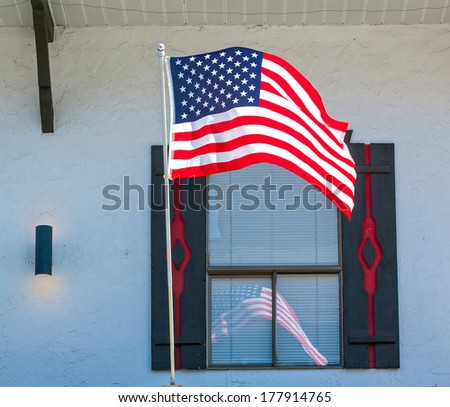 American Flag Reflecting in the Window of a Storefront in Leavenworth WA USA - stock photo