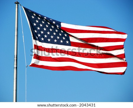 American flag sailing in the wind over blue sky