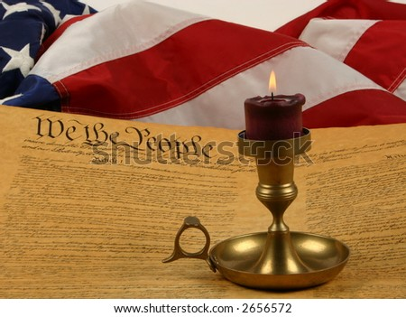 American Flag, the Constitution, and a burning candle - stock photo