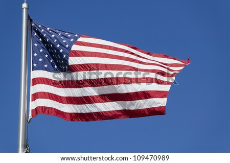 American flag waves in the wind against a blue sky - stock photo