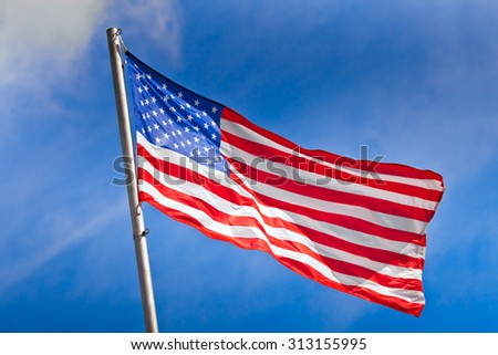 American flag waving against the blue sky - stock photo