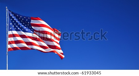 American flag waving in blue sky - stock photo