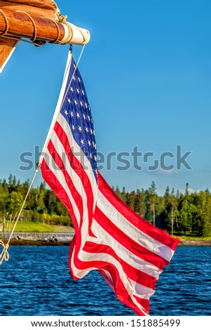 American flag waving in the breeze off a sailboat on water against blue sky with copy space - stock photo
