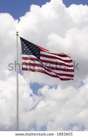 American flag waving in the wind with a beautiful cloud formation behind it - vertical shot - stock photo