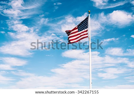 American flag waving under a blue sky - stock photo