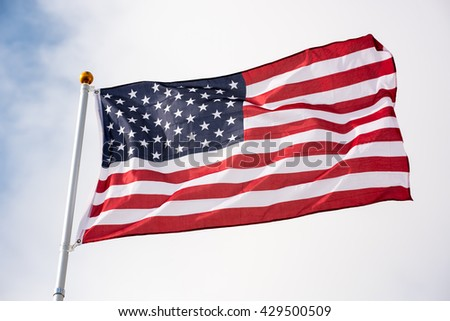 American flag waving with the wind on a cloudy day.