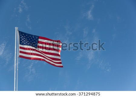 American Flag with Blue Sky and Light Clouds Behind