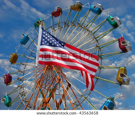 American flag with carnival ride in background - stock photo