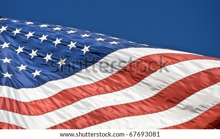American flag with dark blue sky background - stock photo