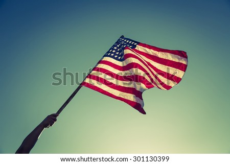 American flag with stars and stripes hold with hands against blue sky ( Filtered image processed vintage effect. ) - stock photo