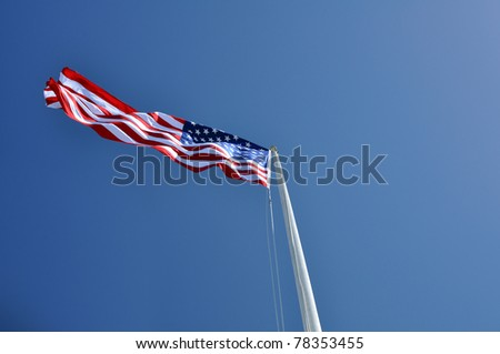 American flag with sun and blue sky behind - stock photo
