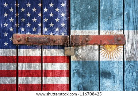 American flag with the Argentine flag on the background of old locked doors - stock photo