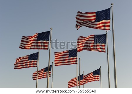 American flags flapping in the wind against a clear blue sky - stock photo