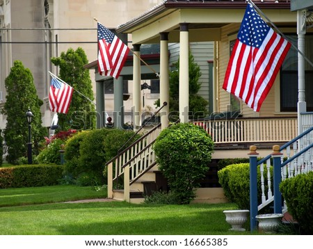 American flags flying proudly on front porches of a small town during a holiday - stock photo