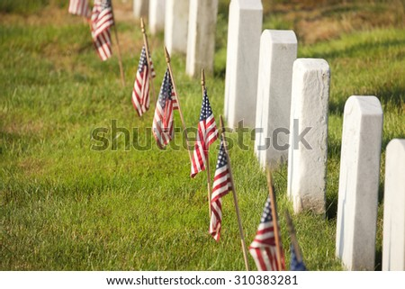 American flags near gravestones at Arlington National Cemetery in Virginia - stock photo