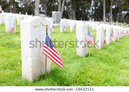 American flags on tombstones in cemetery at memorial day remembrance - stock photo