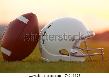 American Football and Helmet on the Field at Sunset - stock photo