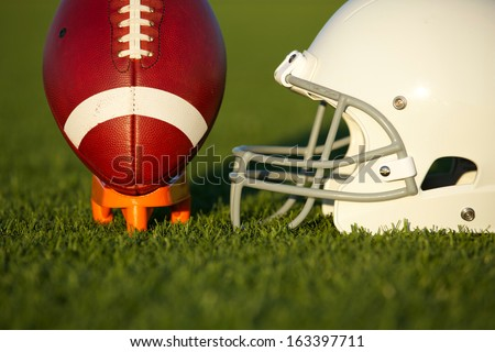 American Football and Helmet on the Field with Ball Teed Up - stock photo