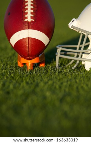 American Football and Helmet on the Field with the Ball Teed Up - stock photo