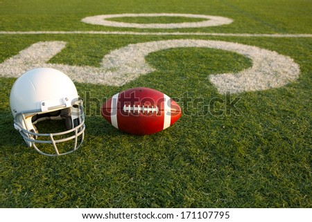 American Football and Helmet on the Field with the Fifty Yard Line in the Background - stock photo