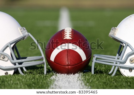 American Football and Helmets on the Field - stock photo