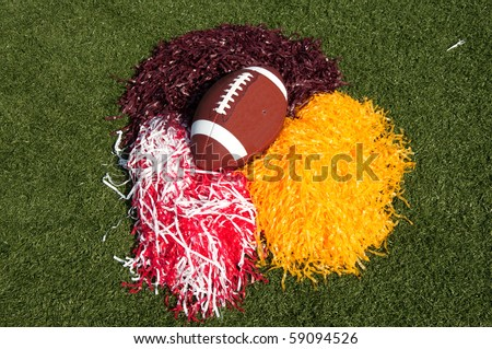 American football and pom poms on field. - stock photo