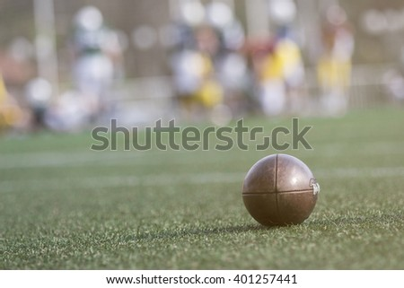 American football ball and players in the background