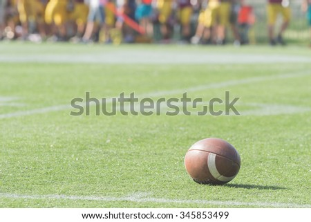 American football ball on the court with defocused players in the background.
