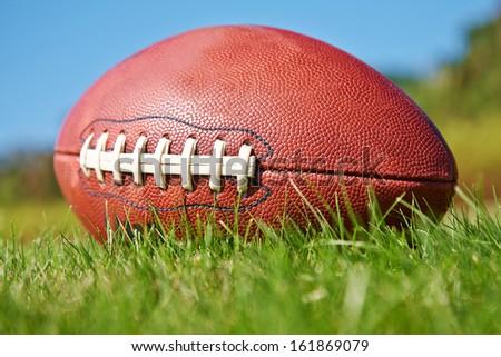 American football ball on the grass - stock photo