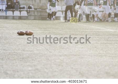 American football balls on green grass field  - stock photo
