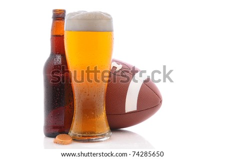 American Football behind a bottle and glass of beer with condensation. Horizontal format on a white background with reflection. Great for Bowl Game projects. - stock photo