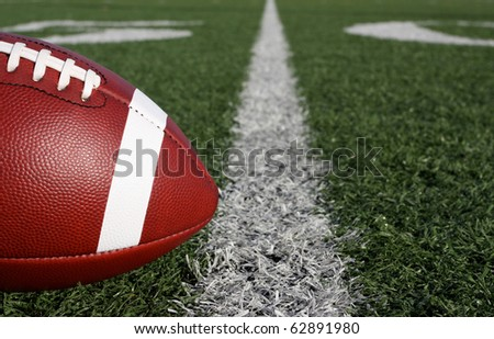 American Football close up with the Fifty Yard Line Beyond - stock photo
