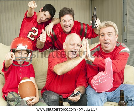 American football fans get together for a super bowl party. - stock photo