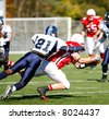 American football game. Running back dives for first down versus defender. - stock photo