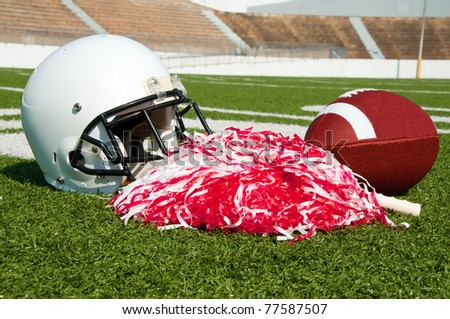 American football, helmet, and pom poms on field in stadium. - stock photo