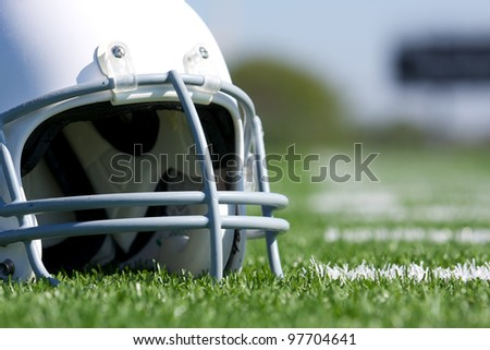 American Football Helmet Close Up on the Field with room for copy - stock photo