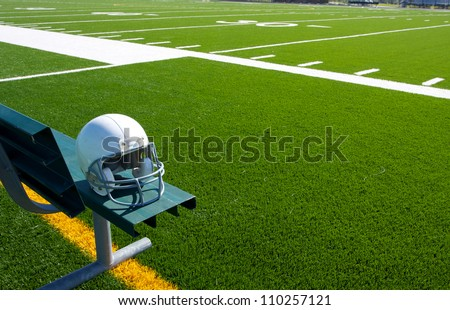 American Football Helmet on the Bench with the field beyond - stock photo